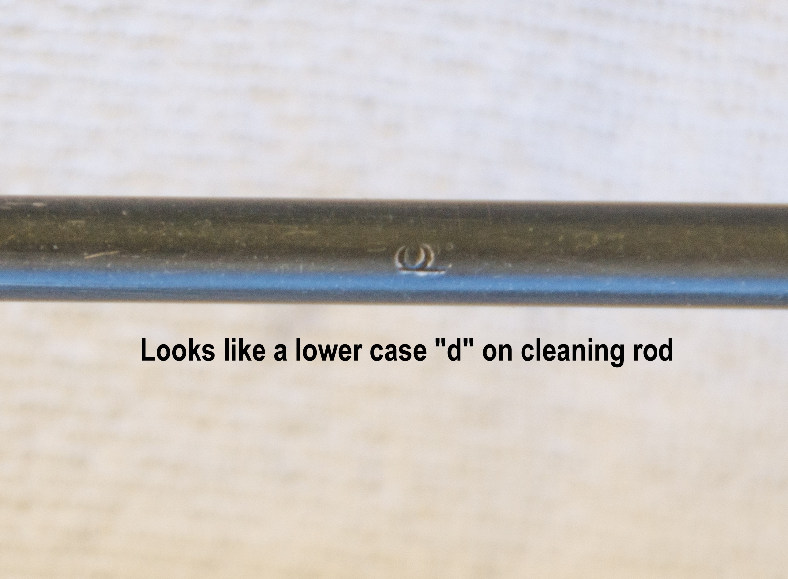 "lower case ""d"" on cleaning rod"